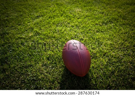 american football on stadium with out of focus players in the background - stock photo
