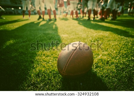 american football on stadium with out of focus players in the background - sport concept - stock photo