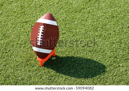American football on tee sitting on field with afternoon shadow showing. - stock photo