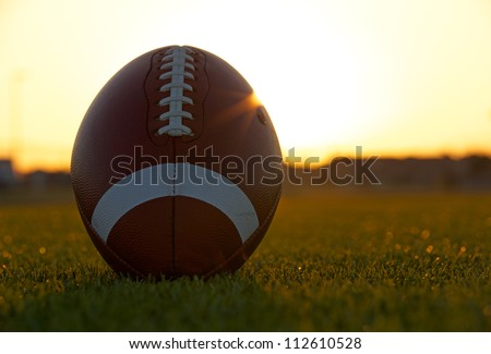 American Football on the Field backlit by the sun with room for copy - stock photo