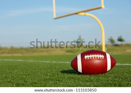 American Football on the Field with Goal Posts beyond - stock photo