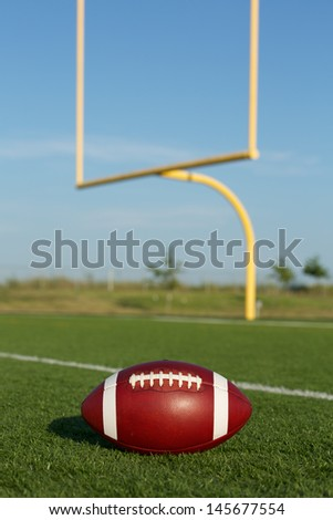 American Football on the Field with Goalposts beyond - stock photo