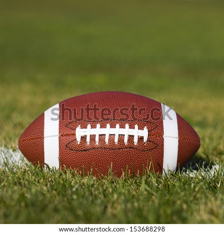 American Football on the field with green grass  - stock photo