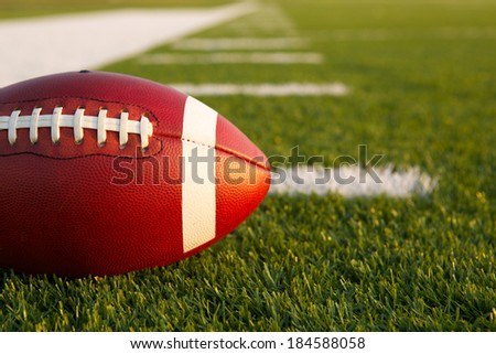 American Football on the Field with Yardlines Beyond - stock photo