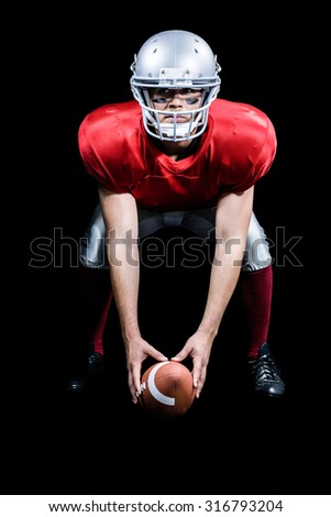American football player bending while holding ball against black background - stock photo