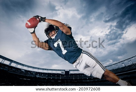 American Football Player Catching a touchdown Pass - stock photo