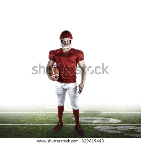 American football player holding ball against american football pitch