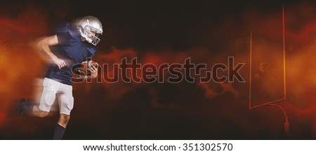 American football player holding ball in mid-air against dark background