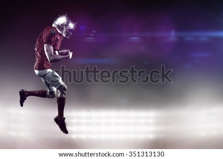 American football player holding ball while running against spotlight