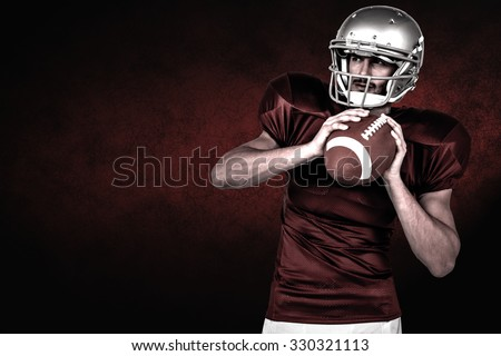 American football player holding ball white looking away against dark background