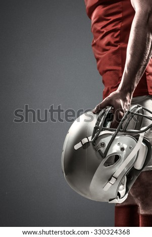 American football player holding helmet against grey