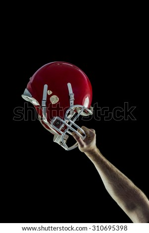 American football player holding up his helmet against black background