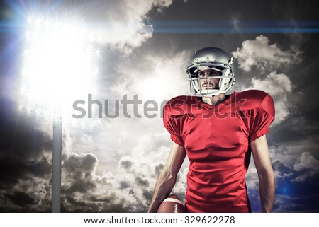 American football player in red jersey looking away against spotlight in sky