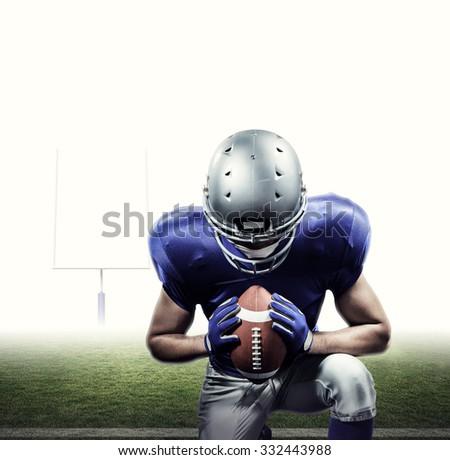 American football player kneeling against american football posts - stock photo