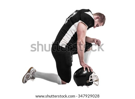 American football player, knelt on one knee, head bowed. Isolated on white background.