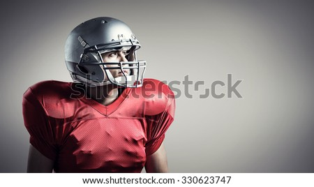 American football player looking away while standing against grey vignette