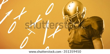 American football player looking down against orange background - stock photo