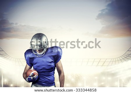American football player looking down while holding ball against rugby stadium
