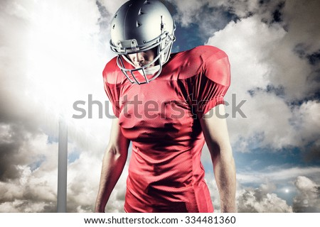 American football player looking down while standing against spotlight in sky