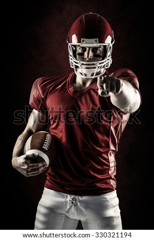 American football player pointing at camera against dark background