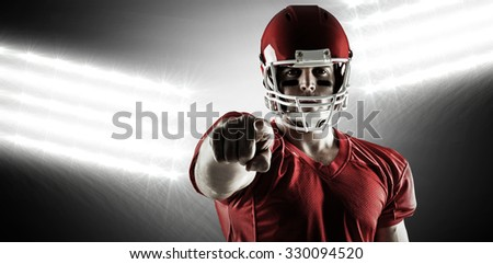 American football player pointing at camera against spotlight