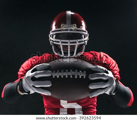 American football player posing with ball on black background - stock photo