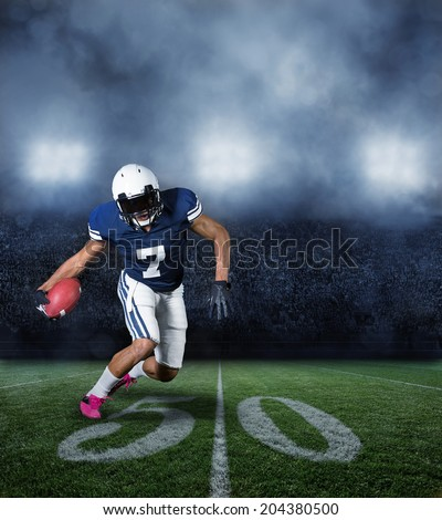 American Football Player running with the ball in a large stadium - stock photo