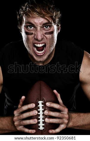 American football player screaming aggressive holding american football on black background. Strong fit Caucasian fitness man. - stock photo