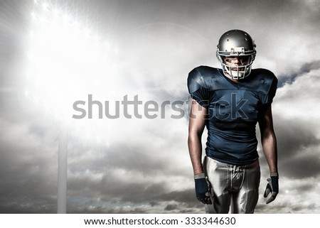 American football player standing against spotlight in sky