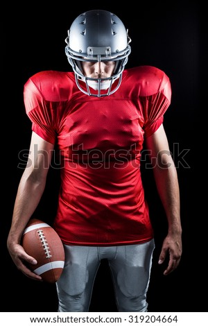 American football player standing with ball against black background