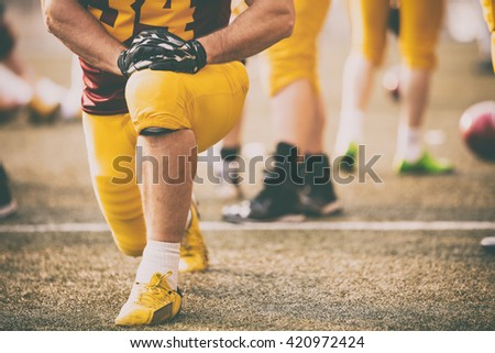 American football player stretching before entering the game. - stock photo