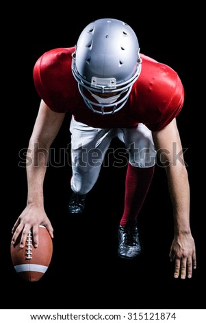 American football player taking position while holding ball against black background - stock photo