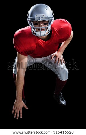 American football player taking position while playing against black background - stock photo
