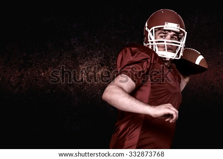 American football player throwing a ball against dark background