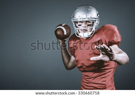 American football player throwing ball against blue