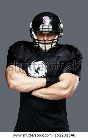 American football player wearing helmet and black jersey with number - stock photo