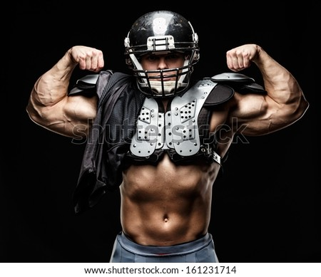 American football player wearing helmet and protective armour  - stock photo