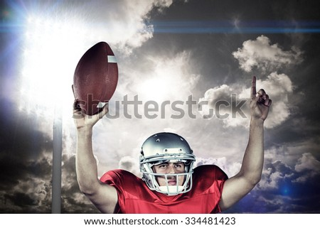 American football player with arms raised holding ball against spotlight in sky