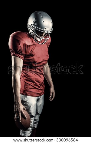 American football player with ball looking down against black