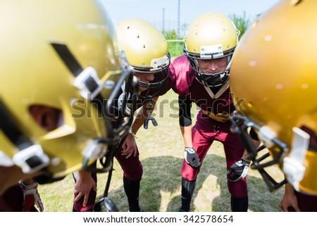American Football players at strategy huddle - stock photo