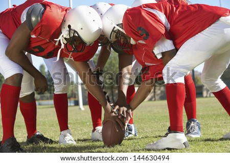 American football players in a huddle around the ball on field - stock photo