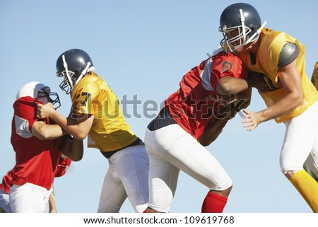 American football players tackling each other against clear sky - stock photo