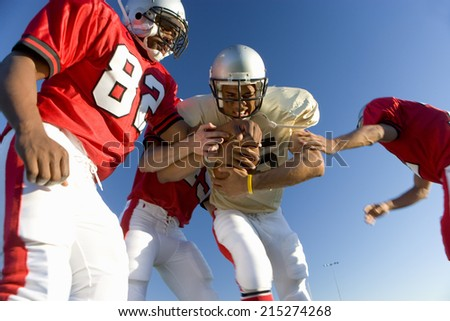 American football players tackling opposing player with ball, low angle view