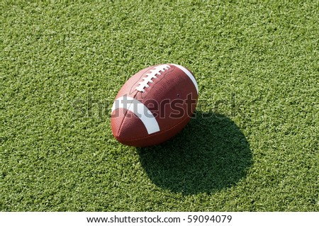 American football sitting on field with afternoon shadow showing.