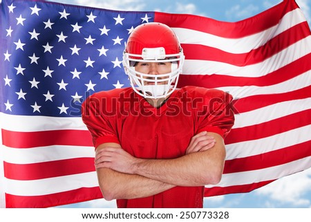 American Football Sportsman Player Standing In Front Of American Flag - stock photo