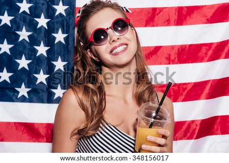 American girl. Cheerful young woman holding a cup of juice and wearing sunglasses while standing against American national flag