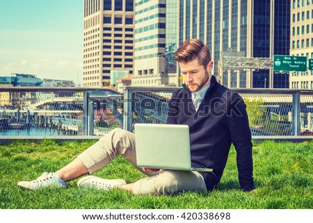 American graduate student traveling, studying in New York. Wearing black sweater, tan pants, white sneakers, a guy with beard, sitting on green lawn in business district, working on laptop computer.  - stock photo