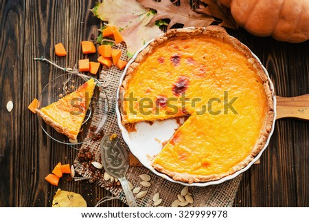 American homemade pumpkin pie , pumpkin seeds and autumn leaves on a wooden background - stock photo