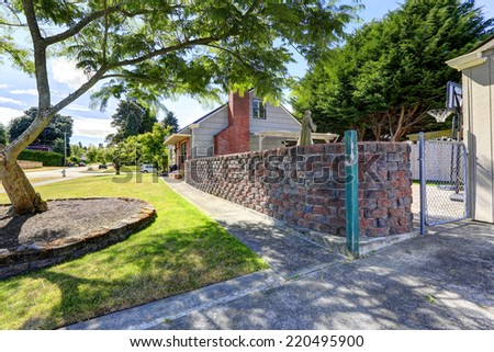 American house exterior with brick wall trim and stone wall to separate backyard from front yard - stock photo