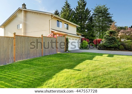 American house with beautiful curb appeal. View of car garage, wooden fence and driveway - stock photo